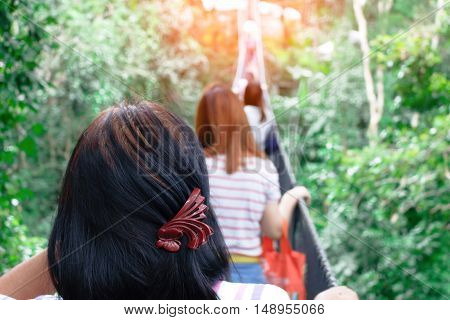 Woman doing tree climbing in adventure park with greenery in background on summer day. Happy female adventure climbing high wire park and safety equipment.