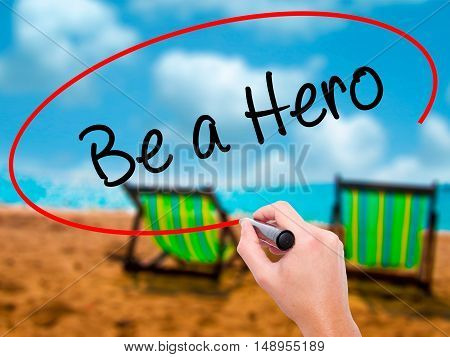 Man Hand Writing Be A Hero  With Black Marker On Visual Screen