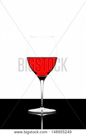 red wine glass on a black board isolated and backlit with reflection