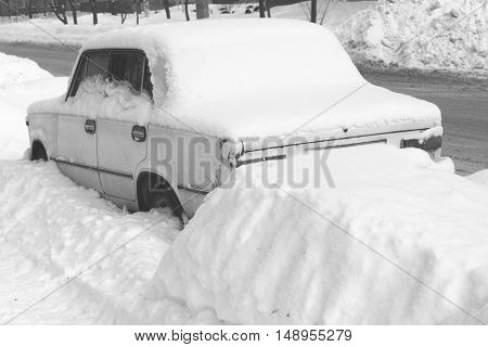 Old car in winter in snow on road, black and white photo