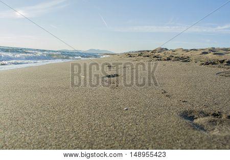 Footprints on the beautiful sandy beach with waves crashing