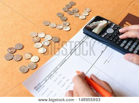 Close up of man with calculator counting making notes at home coins on table is text