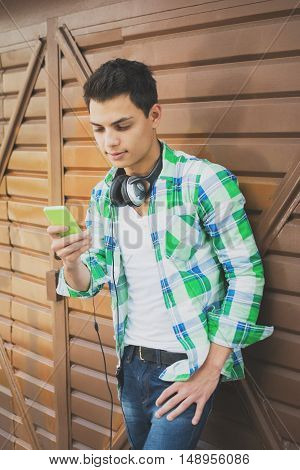Modern young mixed race millennial brunet man with smart phones and headphones, standing by garage door, looking at cellphone, texting. Matte color filter applied.