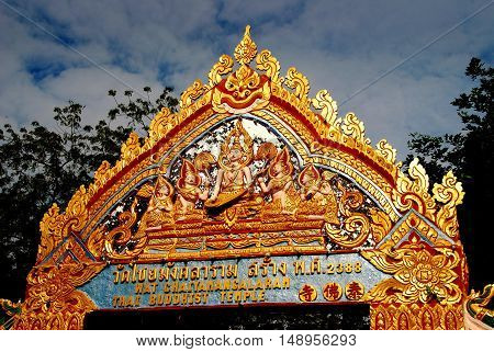 Georgetown Malaysia - January 8 2008: Ornate gilded entry gate with carved Buddha figures at Wat Chaiyamangalaram Thai Buddhist Temple *