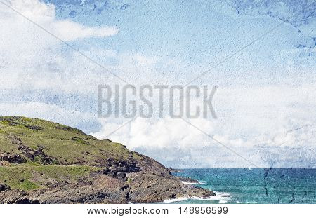 Grassy, rocky coastline and aqua ocean waters. Vintage, grunge textured image with copy space for text