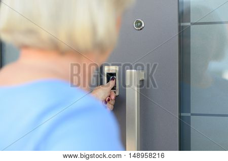 Woman using scanner to read her thumb print to gain electronic access to a door close up over the shoulder view