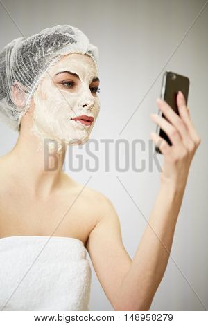 Portrait of woman with cosmetic mask on face and mesh hair cap on head talking phone in beauty salon.