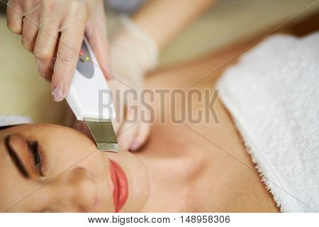 Beautician hands in rubber gloves do ultrasonic skin cleaning on face of woman lying on couch in beauty salon.