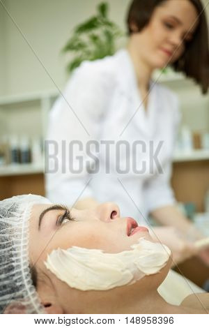 Cheek with portion of cosmetic mask on face of woman lying on couch in beauty salon, beautician stands on background out of focus.