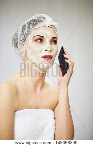 Portrait of woman with cosmetic mask on face and mesh hair cap on head sitting on couch and talking phone in beauty salon.