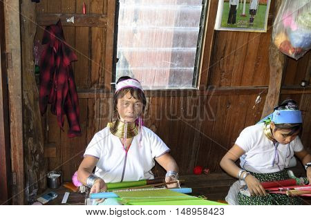 INLE LAKE, MYANMAR - NOVEMBER 02: Long necked Kayan Padaung women weaves silk on a loom in their store at the Inle Lake on November 2, 2015 on Inle Lake, Myanmar (BURMA).