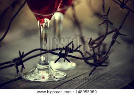 Rusty barbed wire and glasses with red wine on a table. Alcoholic dependence.