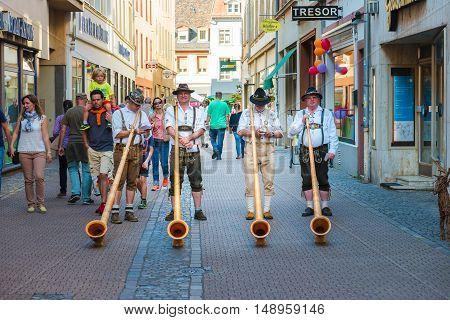 Alphorn player in traditional Bavarian costumes performing on the street of Heidelberg at the fall folk festival - September 24 2016, Heidelberg, Germany