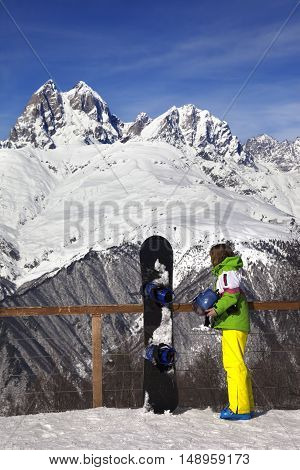 Young snowboarder with helmet in hands and snowboard on viewpoint in winter mountain at sun day. Caucasus Mountains. Hatsvali Svaneti region of Georgia.