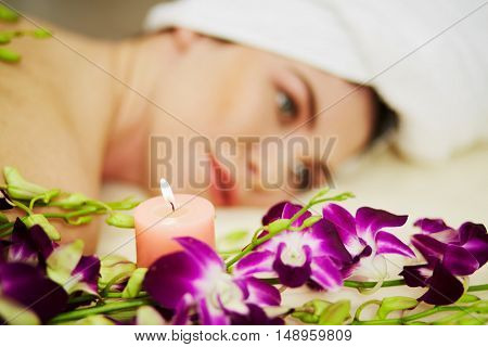 Shoulders and face of woman that lies among orchids and burning candles on couch in beauty salon, focus on candle.