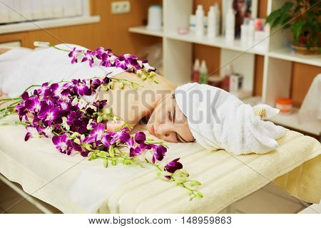Woman lies on couch with flowers and burning candle in beauty salon.