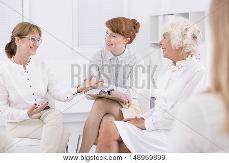 Woman with glasses talking to her friends in bright interior