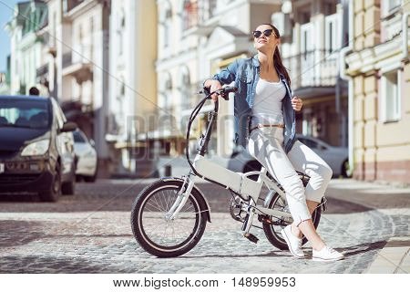 Have a ride. Delighted smiling beautiful woman sitting on the bicycle and going to ride while resting outside