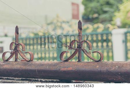 vintage tone image of old iron sharp tip on fence.