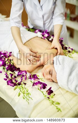 Female massage therapist massage back of woman lies on couch with flowers in beauty salon.