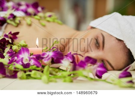 Woman lies on couch among flowers and looks at burning candle in beauty salon, focus on candle.