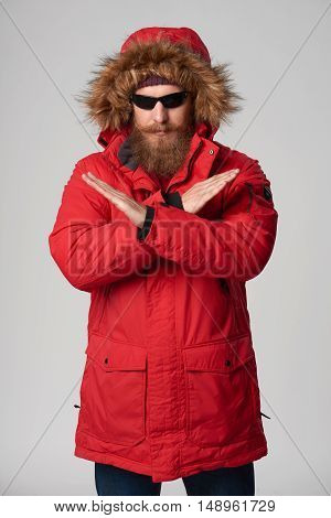 Portrait of a serious bearded man wearing red winter jacket and sunglasses with hood on, gesturing stop enough hand sign, studio shot