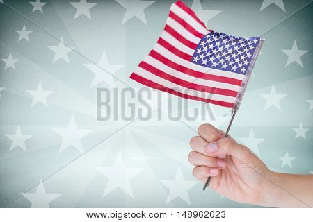 Cropped image of hand holding American flag against starry background