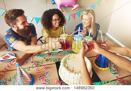 Happy friends holding drinks over cake from high angle view with party decorations on table