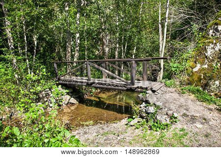 Small bridge lets hikers cross a  stream in a wooded area of Uvac . Serbia.
