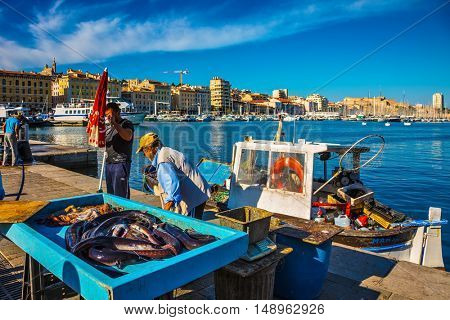 MARSEILLE, FRANCE - MAY 23, 2015: The morning fish market in the old port of Marseilles. Fishermen are laid out on the counter fresh catch
