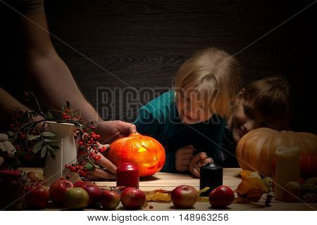 Male hands put on a festive table Halloween pumpkin glowing. Children delighted look on pumpkin