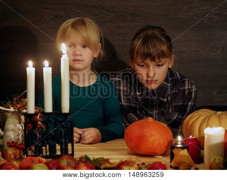 Children at the festive table fascinated looking at the candles. Halloween. On the table pumpkins apples decorations for the holiday