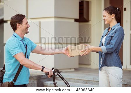 That is for you. Cheerful smiling professional courier holding a box and delivering parcel while using a bicycle
