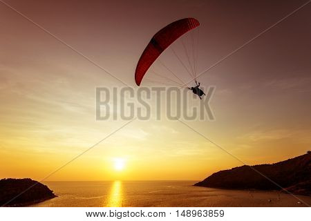 Silhouette of skydiver flies on background of sunset sky and sea. Phuket island, Thailand