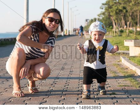 Mom and son playing near the ocean at sunset. In a very beautiful baby funny facial expression.