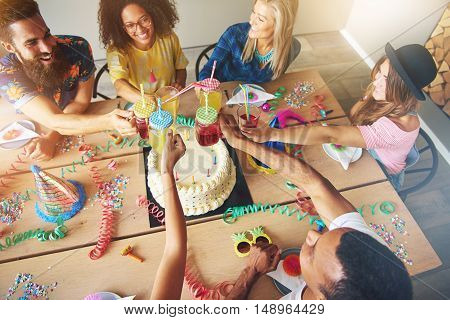 View from above on group of adults sitting at large wooden table around birthday cake