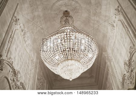 Burning chandelier on ceiling in narrow room.
