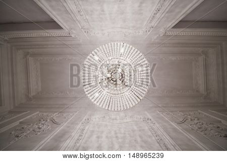 Burning chandelier on ceiling in narrow room, view from below.