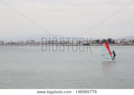 Guy Windsurfing Near The Coast In Spain In A Cloudy Day