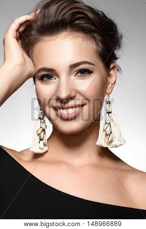 Portrait Of A Girl With A Charming Smile In A Black Dress And Earrings Tassels
