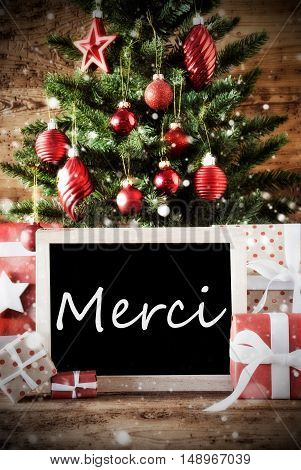 Christmas Card For Seasons Greetings. Christmas Tree With Balls. Gifts Or Presents In The Front Of Wooden Background. Chalkboard With French Text Merci Means Thank You