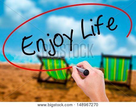 Man Hand Writing Enjoy Life With Black Marker On Visual Screen