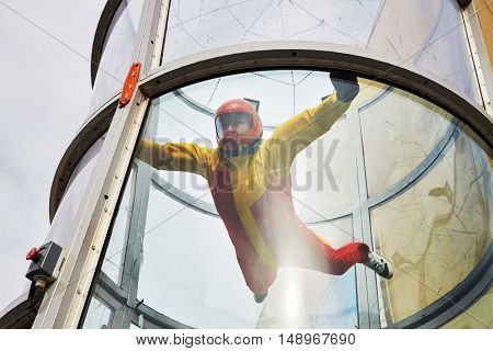 Woman in helmet and red-yellow suit flies in air-tube with glass walls.