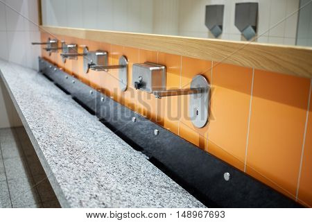 Large washbasin with several faucets and mirror above.