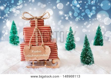 Sleigh Or Sled With Christmas Gifts Or Presents. Snowy Scenery With Snow And Trees. Blue Sparkling Background With Bokeh Effect. Label With German Text Frohe Weihnachten Means Merry Christmas
