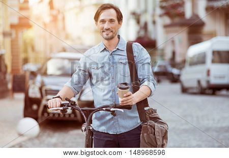 Boost your energy. Delighted bearded adult man drinking coffee and holding a bicycle while walking along the street