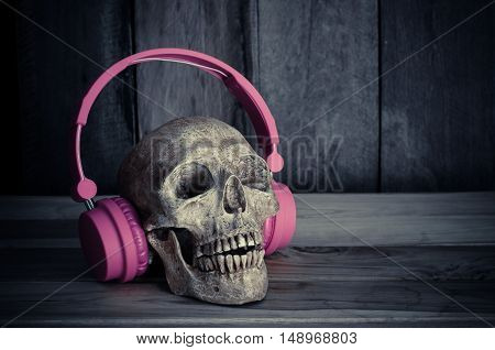Still life human skull model with pink headphones on wooden background.