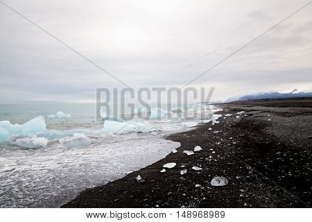 Beautiful beach in South Iceland with black lava sand and icebergs