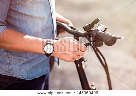 Best vehicle. Pleasant man holding handle of the bicycle while going to ride