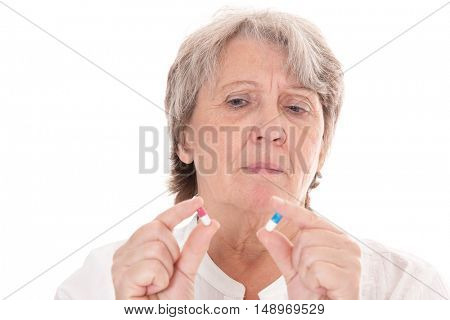 Old age woman checking two pills
